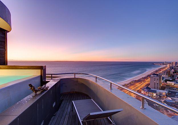 The Penthouse On Beach spog met die pragtigste Kaapse uitsig met die wye oseaan aan die een kant en die stadsliggies aan die ander kant.