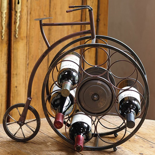 """Fun way to display your Wine! Exploring wine country by bicycle is so much more flavorful.This vintage-style high-wheeler holds seven bottles in its spokes for handsome storage in your kitchen or bar. Made of metal with a glazed rust finish. Holds wine bottles up to 31/4"""" diam. Imported. 19½ x 6½ x 18¾"""" h."""