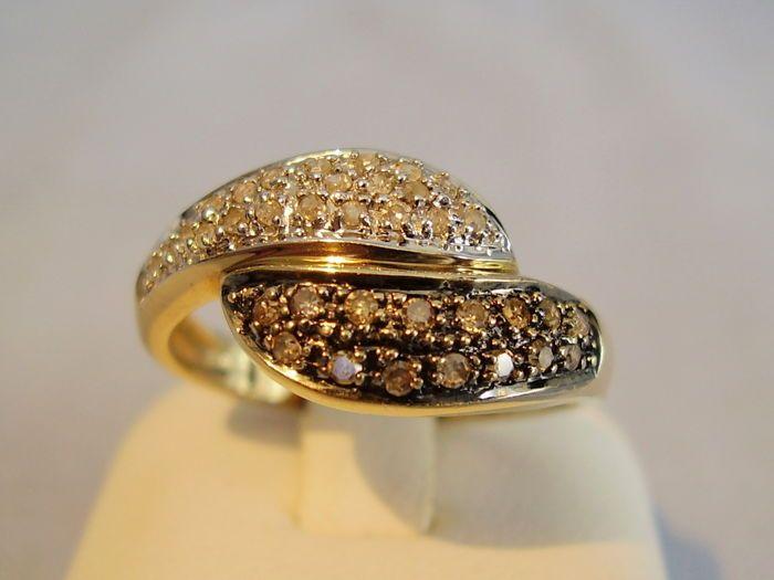 """Gouden cocktail ring met witte en bruine diamanten van 072 ct in totaal.  De ring is gemaakt van 375 = 9 kt geel goud en als zodanig is gestempeld.De kop is gescheiden ring en een helft met 21 witte diamanten is ingesteld de andere helft heeft 15 cognac gekleurde diamanten ze zijn gehouden door zwart uitsteeksels.Alle diamanten zijn 8/8 knippen de witte diamanten zijn W SI de bruine diamanten zijn kleur """"K"""" SI is de totale karaatgewicht 0.72 ct.Ring maat 56/57 = inwendige diameter van de…"""