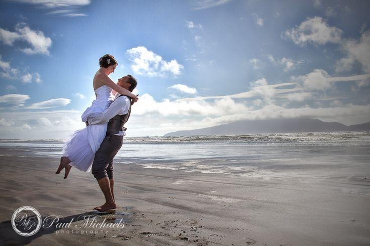 Bride gets a lift on the beach. PaulMichaels Wellington wedding photography http://www.paulmichaels.co.nz/weddings/