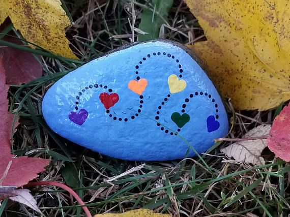 A line of connected rainbow hearts painted rock