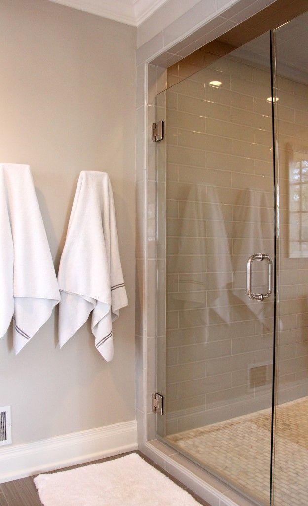Tile: Fabrique Field Tile 6x24 Unpolished Gris Linen; Shower Tile: H Line 4x16 Pumice, H Line Pencil Bullnose Pumice; Shower Floor Tile: Calcutta Gold 1x2 Polished Mosaic; Shower Mosaic Accent: Asian Carrara Mosaic 12x12 and 1/2x12 Polished Cinderella Gray; Shower Door: Clear Glass With Brushed Nickel Hardware