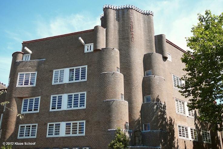De Dageraad was van oorsprong een coöperatie die, gesteund door de sociaal-democratische partij en de vakbeweging, een aantal kruidenierswinkels en bakkerijen, een melkinrichting, een kleermakerij en een algemeen verkoophuis exploiteerde. In 1916 werd ook een woningbouwvereniging opgericht die, in overleg met de gemeente, de taak op zich nam om op het toegewezen terrein 294 volkswoningen neer te zetten. Het woningbouwblok van De Dageraad moest het visitekaartje worden van de…