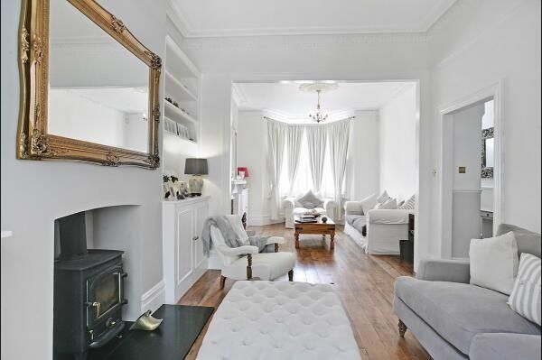We love this sleek grey and white living room colour scheme which gives this traditional Victorian double reception room a modern look and feel. Check out more inspiration at https://www.mybespokeroom.com/ #greyandwhite #livingroom #woodburner