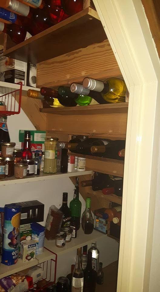Wijnrek onder traptrede in kelderkast.