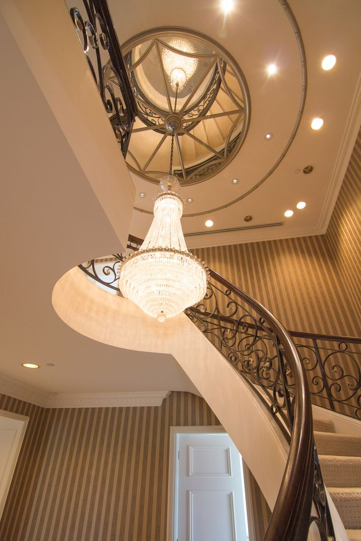 Penthouse spiral staircase, chandelier and mirrored ceiling. Faux wood finish on bannister. Painted by Applied and Decorative Painting www.appliedpainting.com.au. Brisbane, Australia