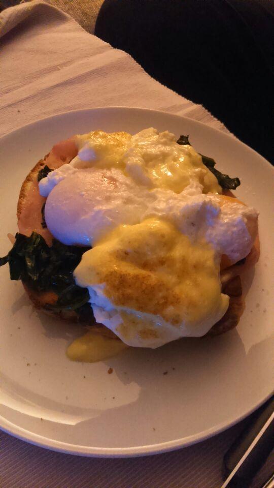 Benedictine eggs with spinach on top of a toast of french bread. Huevos benedictine sobre espinacas salteadas y tostada de pan.