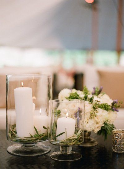 Hurricane-type vases with white pillars and greenery—pine or whatever these are...olive? (SMP - Photography: Megan Sorel Photography - http://www.stylemepretty.com/gallery/picture/1077328/)