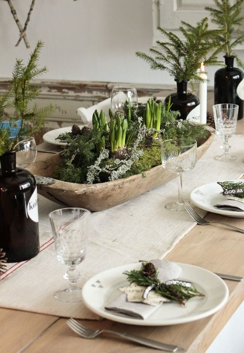 tablescape - French linen, wooden dough bowl with moss and bulbs. Sprigs of evergreen in old bottles.