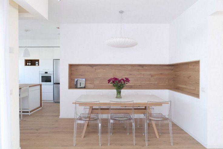 intérieur minimaliste dans la salle à manger blanche avec une niche de rangement en bois, table avec plateau blanc et chaises en acrylique