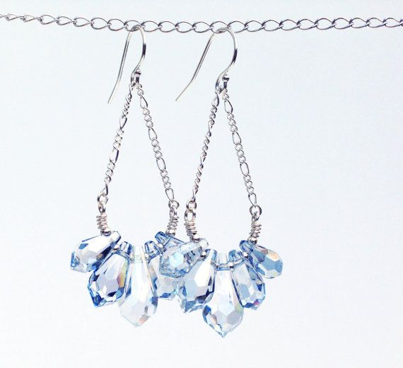 These lovely Swarvoski crystal earrings come in two icy shades, crystal clear and crystal blue shade. They dangle from romantic sterling silver figaro chains. Together they form elegant tear drop shapes that sway beautifully with every motion. Matching necklace available: https://www.etsy.com/ca/listing/386912328  Dimensions: Length without ear hook - 1 3/4 inches Length including ear hook - 2 1/4 inches Width of crystal cluster - 1 inch  Color options: Choose between crystal blue shade and…