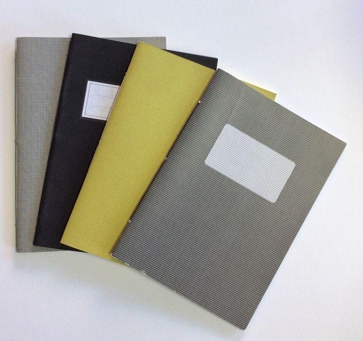 Quaderni rilegati a mano. Da sinistra: Grigio trama tessuto. Nero con etichetta centrale bianca. Verde oliva con trama tessuto. Nero texture con etichetta.