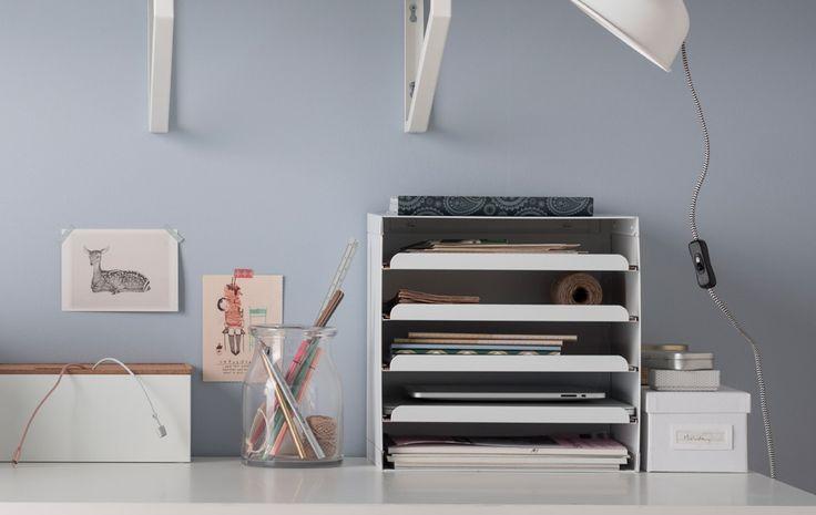 Białe biurko z pomysłami na uporządkowany blat, takimi jak tacka na listy, dokumenty i tablety, pojemniki do przechowywania i kable oraz szklany wazon na długopisy
