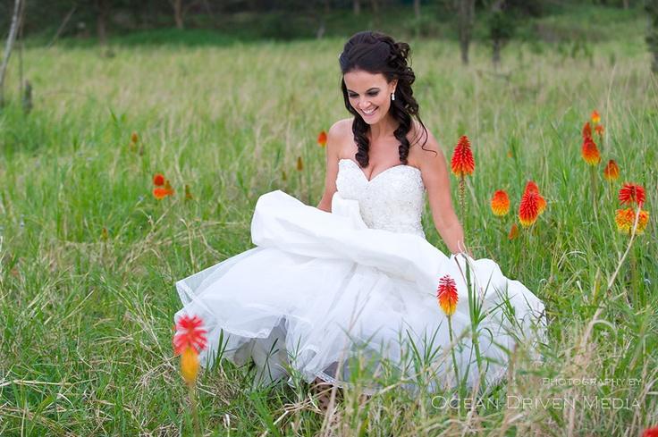 Bride walking through field of pretty flowers
