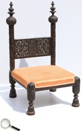 A carved rosewood low nursing chair, with intricate carvings all over. The chair has silk upholstered seating. This piece is from Lucknow.     22 in L x 21 in B x 37 in H