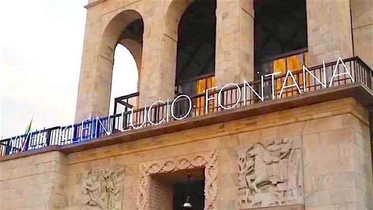 insegne luminose al neon in Piazza Duomo a Milano, titolo della Mostra YVES KLEIN LUCIO FONTANA al Museo del Novecento in Piazza Duomo Milano, giovedi e sabato aperto fino alle 22.30