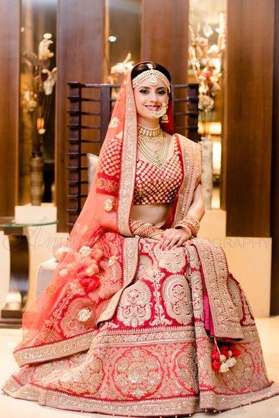 red bridal lehenga , large motif bridal lehenga , red and orange bridal lehenga , elbow length sleeves , matha patti , traditional red lehenga , bridal portrait