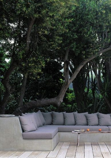 concrete sectional seating under a natural canopy of trees....