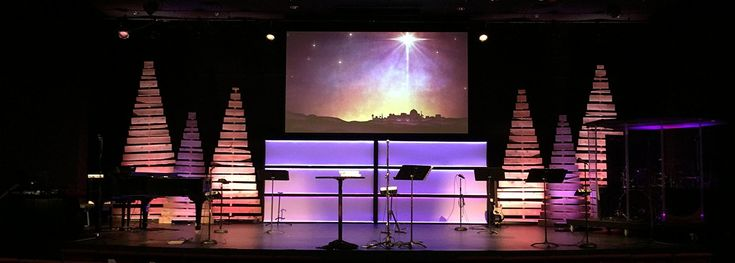 Greg Springer fromFirst Christian ChurchinNorfolk, Nebraska brings us this Christmas design. Inspired by Twinkle Pallet Trees, theycame up with this design. A couple of Greg'sstage team members built and installed these in about 8 hrs. Theylit them using a ADJ RGBA mega bar on each of the 4 largest trees, and a ADJ rgb megabar50 on the smaller 2 trees. Theyused cedar dog-eared fencing materials in 4' and 6' lengths and a 2x4 on edge for the center support. To lay out the tr...