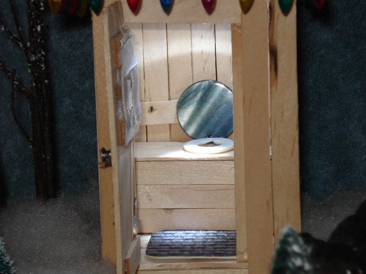 Single seat outhouse made out of popsicle sticks and added accessories