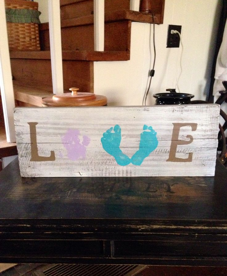 Old wood sign. Baby hand and foot prints. Love