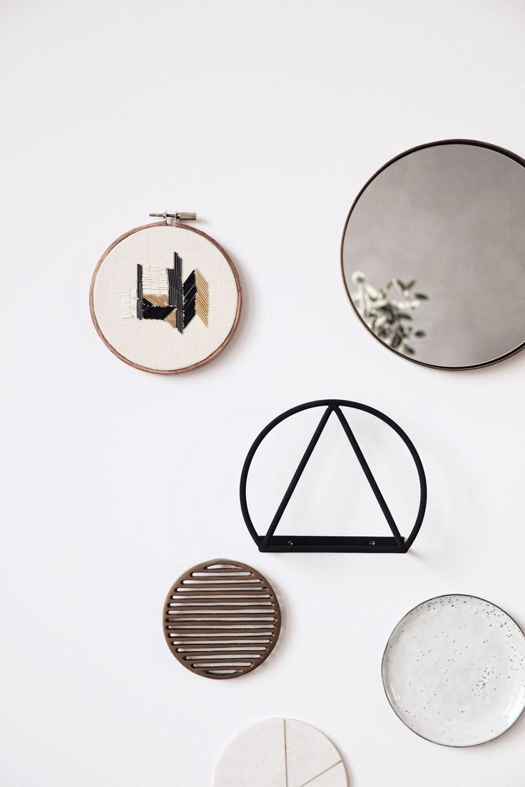 Decorate a wall with a mix of geometrical shapes, materials and colours. To achieve a balanced look, choose a few objects in different colours, and mix them with details in more neutral tones like white and grey. Here, a ceramic plate, a mirror and a metal trivet are used in a new context, and the unexpected mix creates a unique look.
