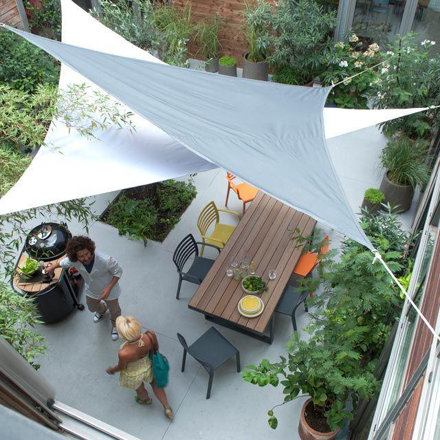 J'aime tout : les toiles tendues modernes, les chaises colorées, la verdure qui entoure la terrasse... Peut-être un bémol pour le sol gris