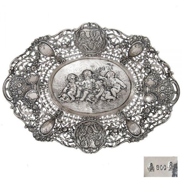 Floreira de prata alemã contrastada. Ao centro quatro crianças aladas. Medalhões superior e inferior