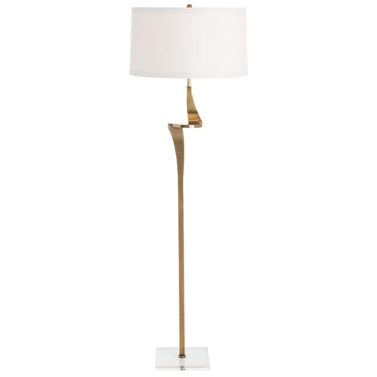 Sculptural form and luxe materials combine in this sinuous floor lamp a single solid twist of antique brass finished steel sits on a clear crystal square
