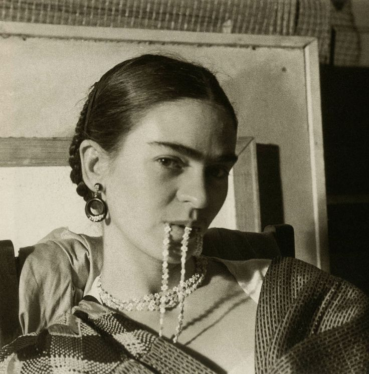 "Photo by Lucienne Bloch, 1933, Frida (26) biting her necklace, New Workers School, NYC. Lucienne said: ""We went to a Spanish restaurant and had a kind of strong stuff like Vodka which one drinks with lemon and salt. We acted most crazy. It was a fine afternoon and cheered Frida up."""