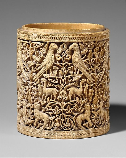 "Ivory cylindrical box; 950–75 AD, Cordoba, Spain; Metropolitan Museum of Art. This ""pyxis"" is carved with intricate detail and densely-packed designs. The symmetry and the interlacing vines create the sense of infinity. The carvings also include typical floral decoration interspersed with animal figures, specifically birds, lions, and gazelles. The main decorative area is bordered on the top and bottom by bands of self-contained repeating designs."