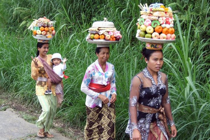 Three Balinese women carry offerings to a Hindu ceremony