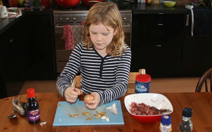 Annemijn is druk een uitje te snijden voor de smoor daging. Een superlekker runderstoof recept uit het boek De geur van witte rijst. Het recept staat op de website Kids in the Kitchen.