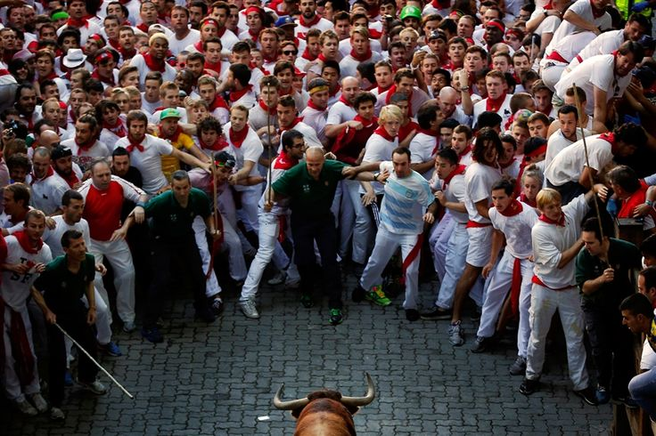 """Daniel Ochoa De Olza / AP Revelers stare at an Alcurrucen's ranch fighting bull during the running of the bulls at the San Fermin festival in Pamplona, Spain, on July 7. People from around the world arrive in Pamplona every year to take part in some of the eight days of the festival, which was glorified in Ernest Hemingway's 1926 novel, """"The Sun Also Rises."""""""
