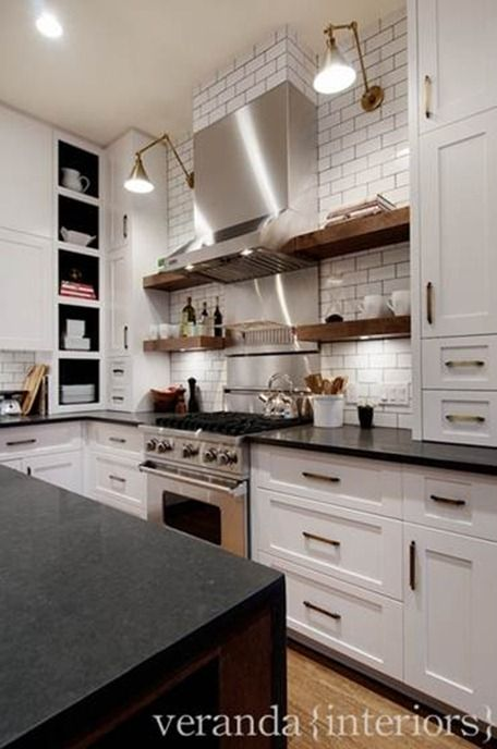 white subway tile gray grout, brass hardware/lighting, black countertops/white cabinets, stainless appliances