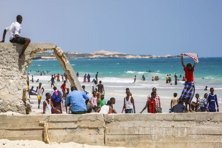 a Somali boy holds a shirt aloft to dry in the wind at Lido Beach in the Abdul-Aziz district of the Somali capital Mogadishu.