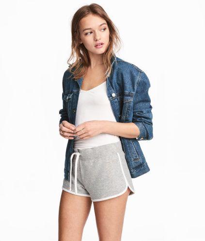 Gråmelerad. Ett par korta shorts i sweatshirtkvalitet med kontrastfärgade kantband. Resår och dragsko i midjan. En bakficka.