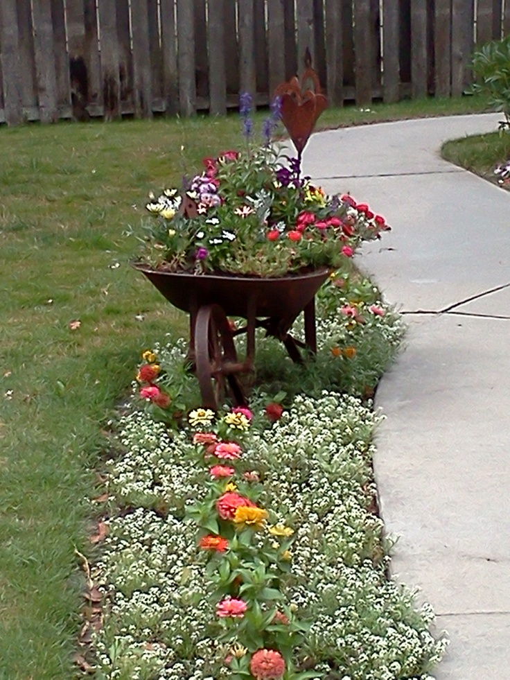 I love the flower landscaping by the sidewalk and the wheelbarrow is a nice touch!