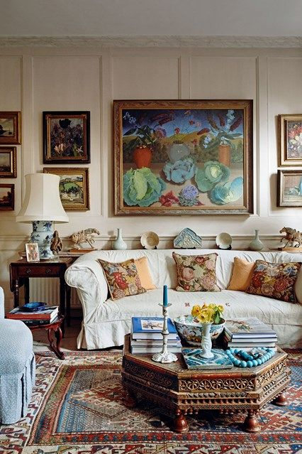 This eclectic living room can be found in the home of Lady Wakefield. It is decorated with needlepoint cushions and pieces of art.