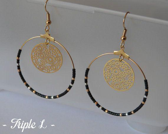 ~ DESCRIPTIF ~ Cette paire de boucles doreilles LUDIVINE est composée de créoles, de perles et dune monture en métal doré pour oreilles percées. Les perles argentées sont plaquées argent 925. Couleurs des perles : noir - argenté - doré. Dimensions : 3,7 cm de diamètre. ~ MATERIEL UTILISE ~ - Crochets doreilles en laiton doré - Créoles en laiton doré - origine : Europe - Perles  ~ ENVOI ~ Les bijoux sont envoyés en courrier suivi dans une enveloppe en papier bulle et soigneusement emballés…