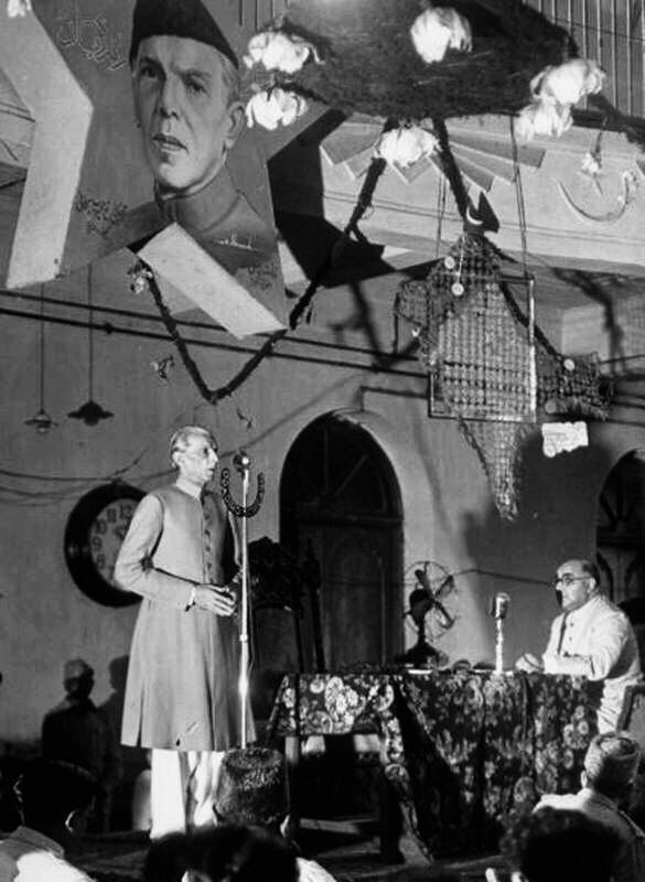 Mohammad Ali Jinnah giving a speech. Liaquat Ali Khan can be seen seated up front.