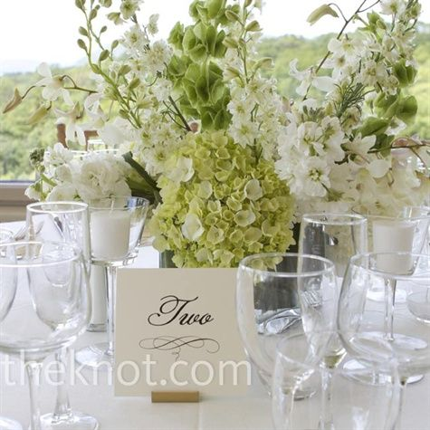 Seasonal flowers like hydrangeas, bells of Ireland, larkspur and dendrobium orchids complemented the white table linens for a fresh, springtime look.: White Centerpieces, Receptions Flowers, White Flowers, Flowers Centerpieces, Formal Wedding, Dendrobium Orchids, Wedding Flowers, Tables Numbers, Tables Linens