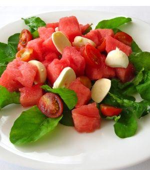 1 fatia média (cerca de 25 g) de melancia sem casca e sem sementes  4 tomates-cereja  20 folhas de rúcula(cerca de 50 g)  25 g de queijo de minas   5 azeitonas pretas   Azeite e manjericão a gosto