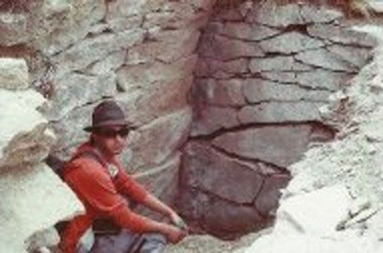 Luis Gutierrez crouched at an entrance to the Pukara Grande situated on its roof.