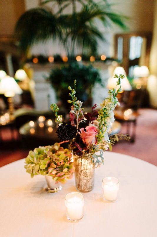 set aglow with votives, this cocktail hour centerpiece featured a hydrangea filled silver julep cup and a mercury glass arrangement of spray roses, dusty miller, loropetalum, burgundy scabiosa, pink rose, larkspur and seeded eucalyptus.