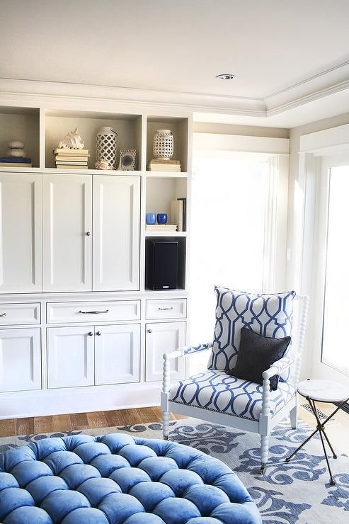 White and blue living room features a round blue velvet tufted ottoman and a white spindle chair on casters upholstered in white and blue trellis fabric atop a grey and blue fleur de lis rug facing a built-in TV cabinet with doors.