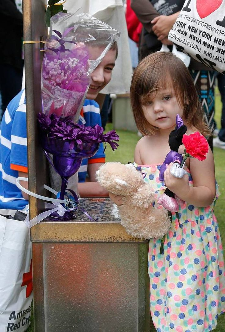 Marlee Hill, 2, a second cousin of Oklahoma City bombing victim Baylee Almon, holds a teddy bear at Almon's chair in the Field of Empty Chairs at the Oklahoma City National Memorial following a ceremony for the 20th anniversary of the Oklahoma City bombing in Oklahoma City, Sunday, April 19, 2015. At left is Broox Kok, who would have been Almon's little brother. About 1,000 people gathered at the former site of the Oklahoma City federal building to commemorate the 20th anniversary of the…