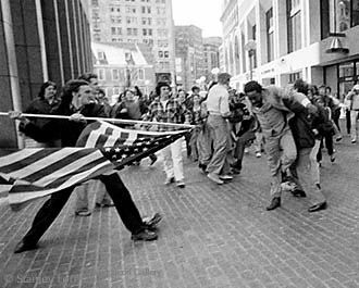 """The Soiling of Of Old Glory,"" by Stanley Forman, Pulitzer Prize, Boston April 5, 1976. A portrait of unthinkable racial hatred, the photograph punctured the nation's comfortable illusion that the struggle over civil rights was primarily a Southern phenomenon, and it crystallized Boston's reputation as a racist city. Following the assault, the man at the center of the frame, is Ted Landsmark, who holds a law degree as well as a doctorate in American Studies, proclaimed that someone tried ""to…"