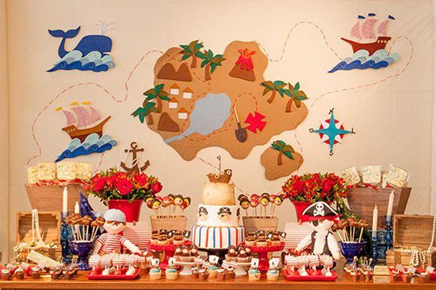 festa pirata infantil com mundo de mapa do teouso, bolo e doces temáticos e enfeites de tesouro.
