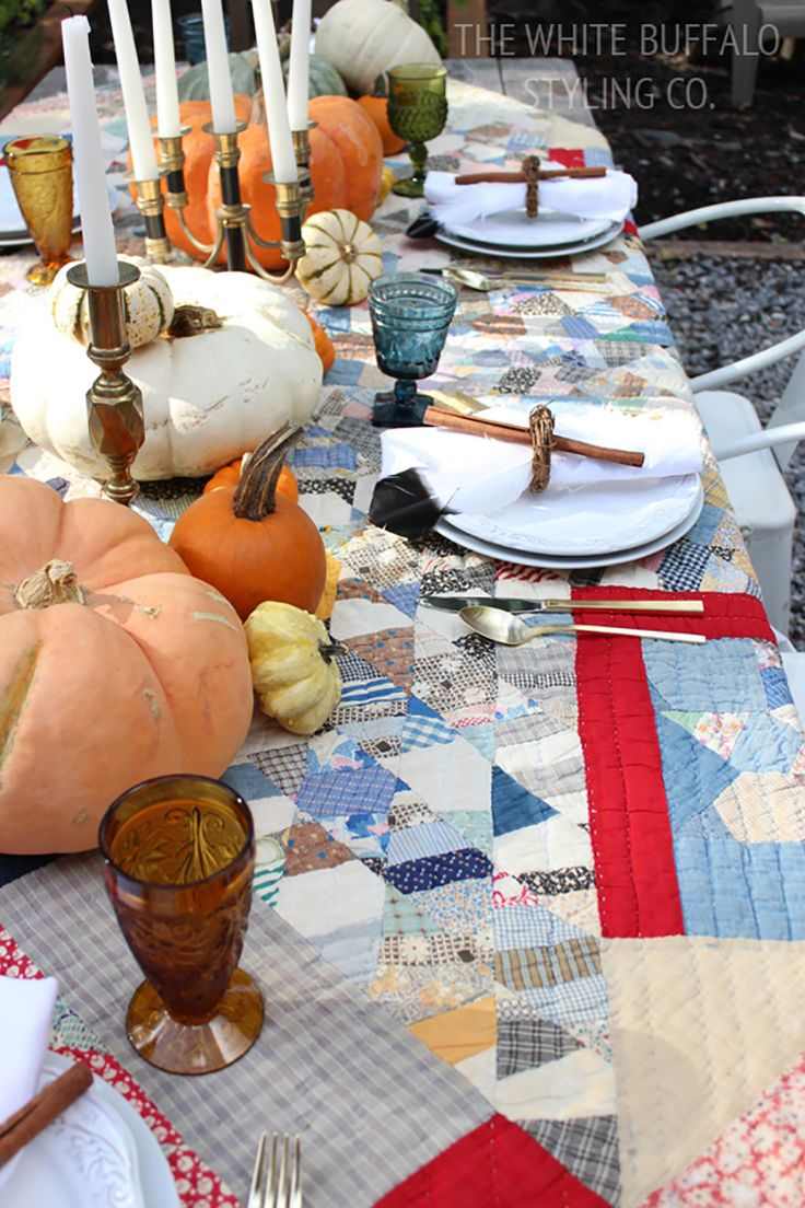 Colorful and country fall table with an old family quilt as the tablecloth with vintage colored glassware and piles of pumpkins #pumpkin #fallparty #entertaining